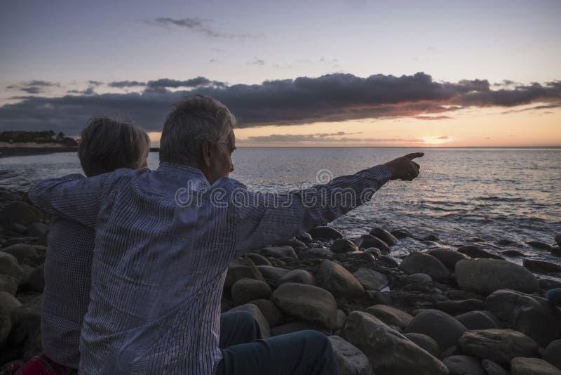 Activit? Romance pour les couples sup?rieurs adultes se reposant ? la plage regardant un coucher du soleil color? sur la mer - va photographie stock