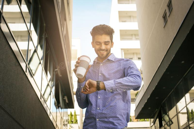 Businessman walking trough street checking the time. stock images