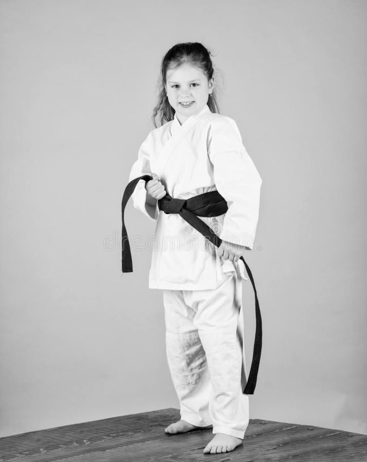 Activity and sport. Karate gives feeling of confidence. Strong and confident kid. Girl little child in white kimono with. Belt. Karate fighter ready to fight royalty free stock image