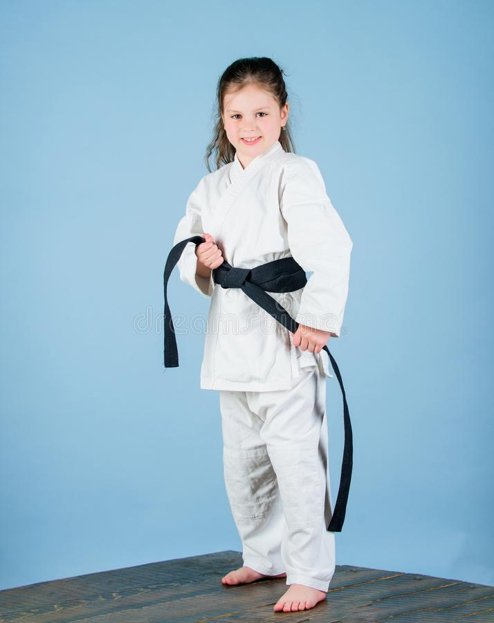 Activity and sport. Karate gives feeling of confidence. Strong and confident kid. Girl little child in white kimono with. Belt. Karate fighter ready to fight stock photo