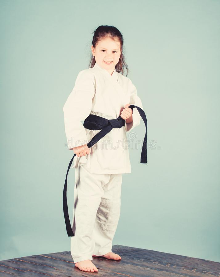 Activity and sport. Karate gives feeling of confidence. Strong and confident kid. Girl little child in white kimono with. Belt. Karate fighter ready to fight stock photos