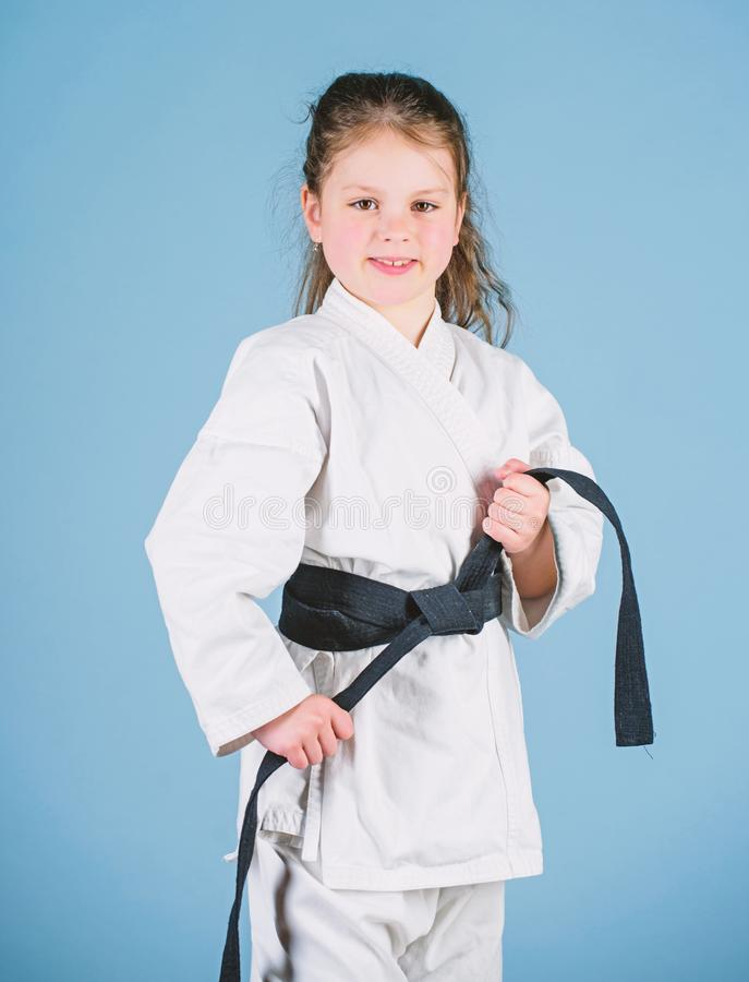 Activity and sport. Strong and confident kid. Girl little child in white kimono with belt. Karate fighter ready to fight. Karate sport concept. Self defence stock photos