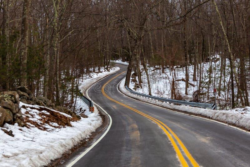 Acton, Stany Zjednoczone, Luty 27, 2019 Lasowa droga z dwoistą żółtą linią w zima czasie, Massachusetts, Stany Zjednoczone obraz royalty free
