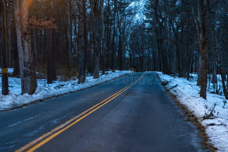 Acton, Stany Zjednoczone, Luty 27, 2019 Lasowa droga z dwoistą żółtą linią w zima czasie, Massachusetts, Stany Zjednoczone zdjęcia stock