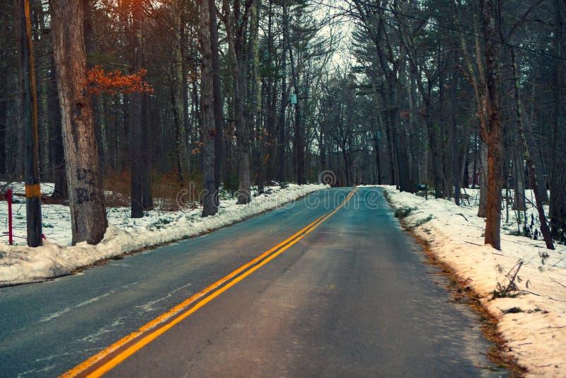 Acton, Stany Zjednoczone, Luty 27, 2019 Lasowa droga z dwoistą żółtą linią w zima czasie, Massachusetts, Stany Zjednoczone fotografia stock