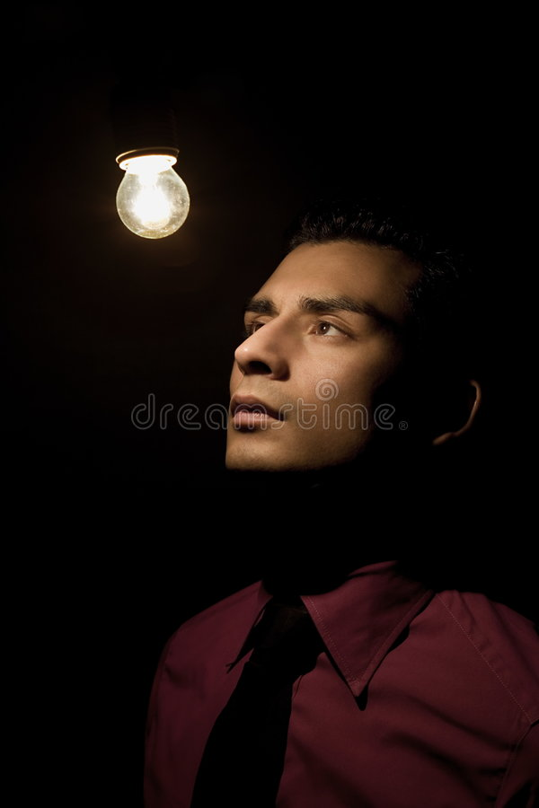 Actor. A young actor dressed as a businessman taking a pose in stage lighting royalty free stock photo