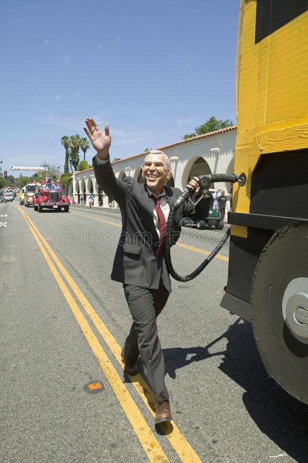 Actor impersonating George W. Bush pumping gas into a Hummer vehicle makes its way down main street during a Fourth of July parade. In Ojai, CA stock photos