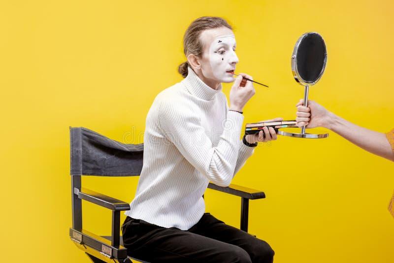 Actor que aplica el maquillaje facial para el funcionamiento de la pantomima foto de archivo