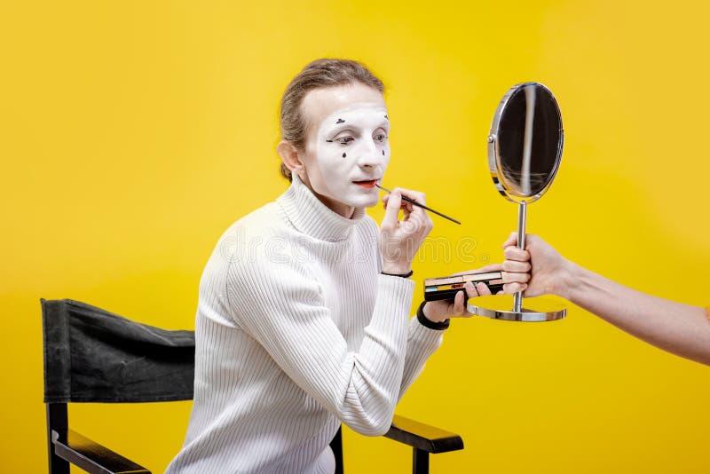 Actor que aplica el maquillaje facial para el funcionamiento de la pantomima fotos de archivo