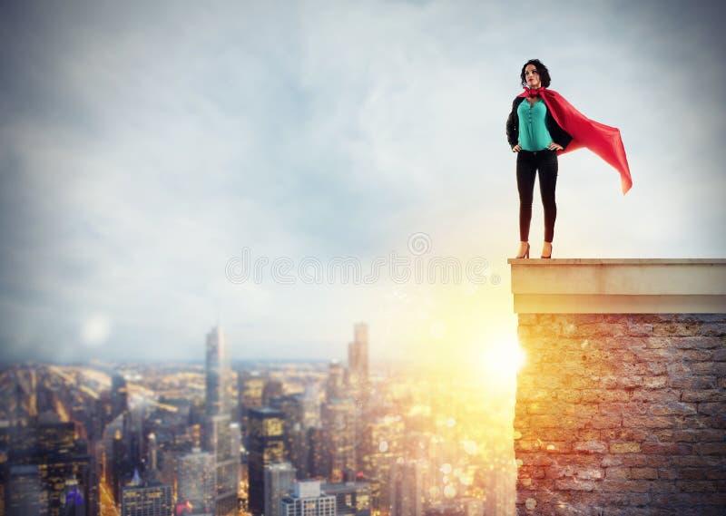 Actos acertados de la empresaria como un superhéroe sobre el tejado de un edificio Concepto de determinación y de éxito imagenes de archivo