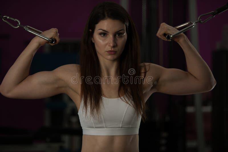 Actove少妇锻炼她的在健身俱乐部健身房的胳膊 免版税库存照片