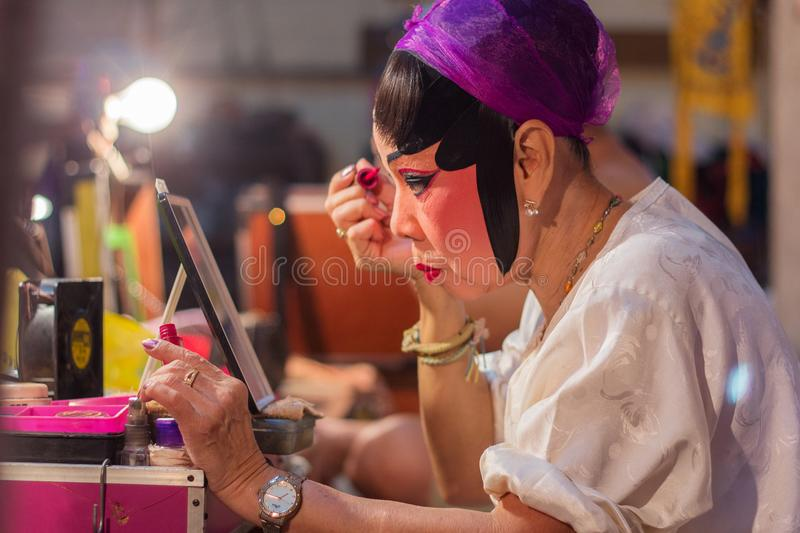 An actress from a Chinese opera group painting mask and putting makeup on her face before the cultural drama and musical performan royalty free stock image