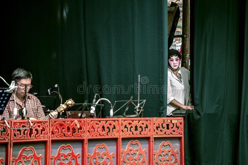 Actress in Chinese Opera on stage. Actress next to orchestra pit on stage during performance of Chinese Opera in Hong Kong