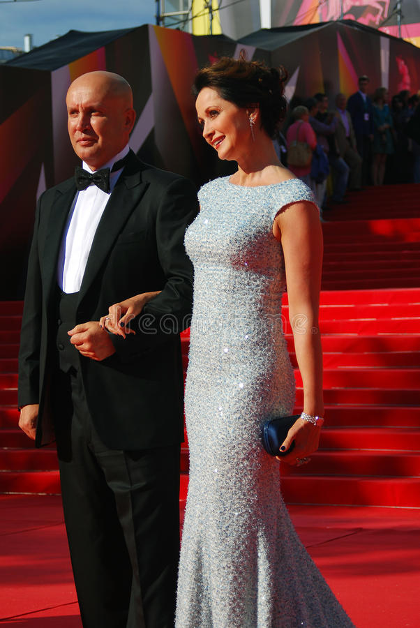 Actress Olga Kabo with her husband pose for photos. Actress Olga Kabo with her husband pose for photos at XXXV Moscow International Film Festival red carpet stock photography
