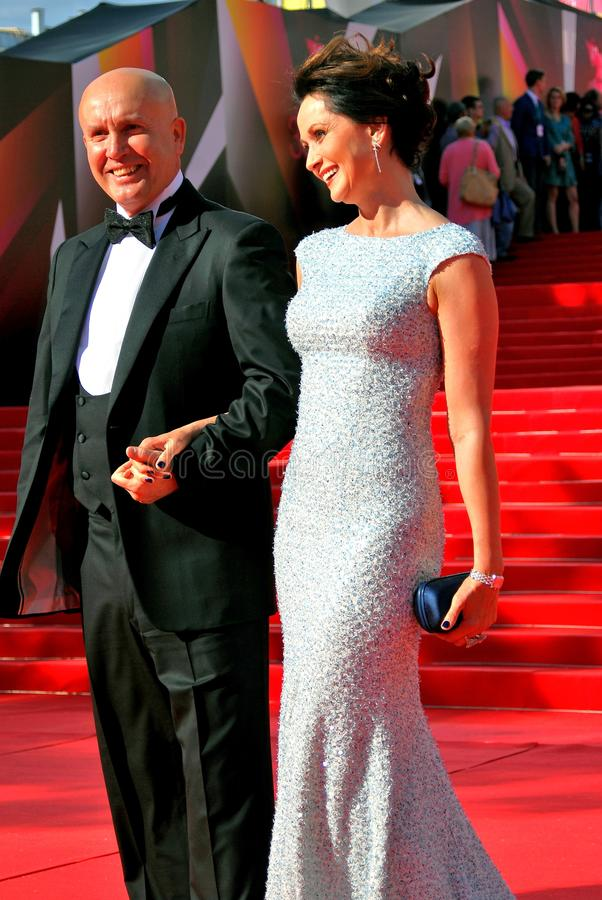 Actress Olga Kabo with her husband pose for photos. Actress Olga Kabo with her husband pose for photos at XXXV Moscow International Film Festival red carpet stock photo