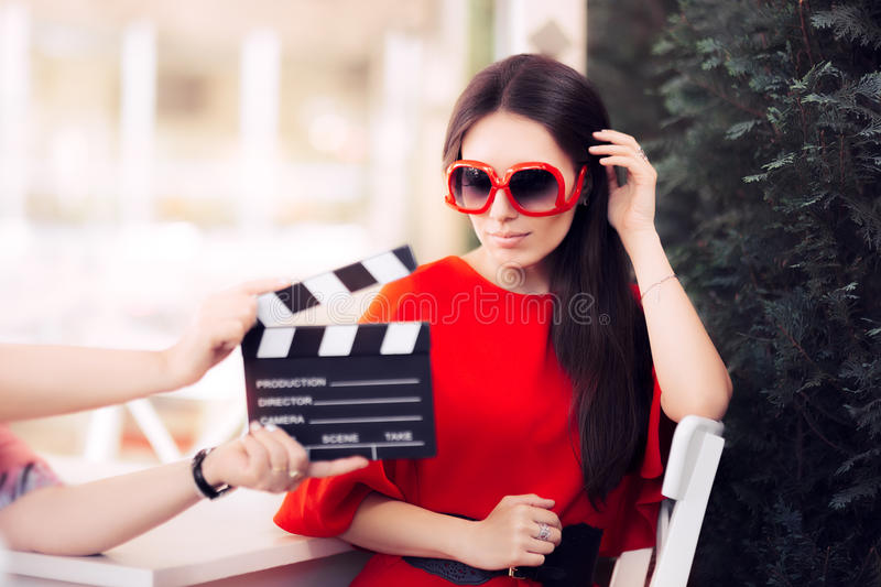 Actress with Oversized Sunglasses Shooting Movie Scene. Diva in red dress and big shades starring in an artistic film stock photography