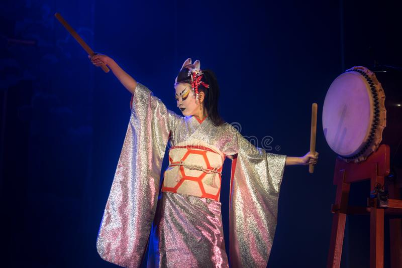 Actress in white traditional japanese stage costume komono hits the drum royalty free stock image