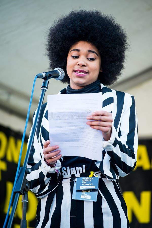 Actress & writer Isabel Adomakoh Young die spreekt tijdens de bijeenkomst van de Women's March op het Trafalgar-plein in Londen,  stock afbeeldingen