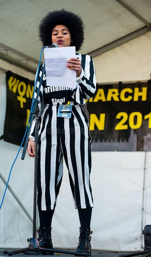 Actress & writer Isabel Adomakoh Young die spreekt tijdens de bijeenkomst van de Women's March op het Trafalgar-plein in Londen,  royalty-vrije stock fotografie
