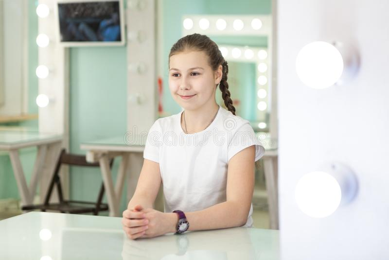 Actrice de l'adolescence de fille d'âge s'asseyant devant le miroir avec des taches légères dans la chambre verte images libres de droits