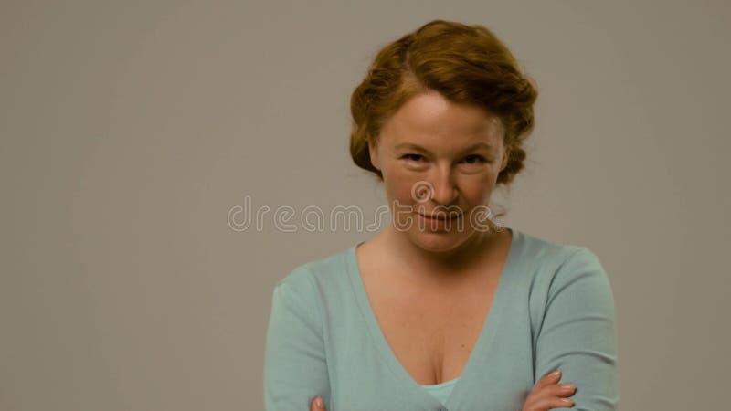 Actrice die van medio leeftijd emoties van irritatie en minachting tonen stock fotografie
