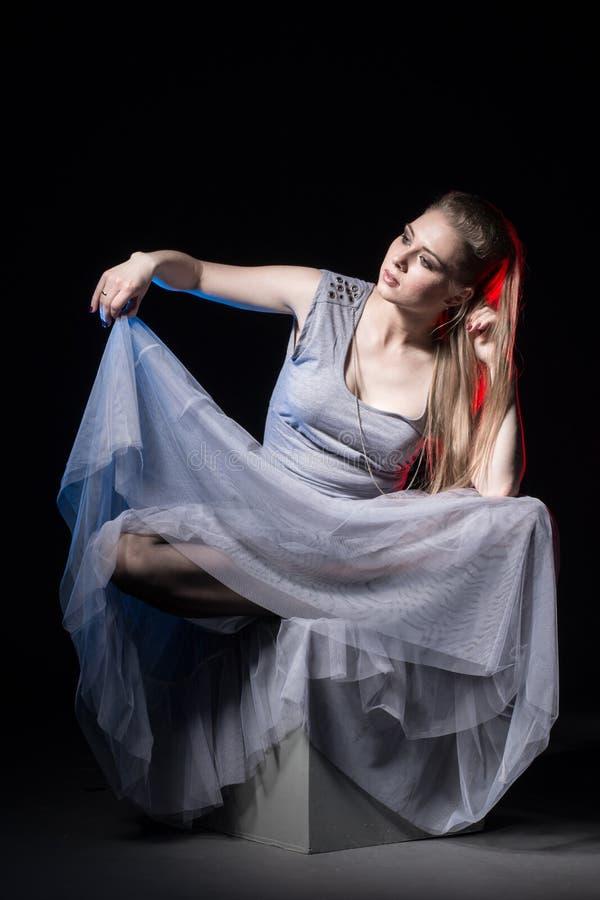 Actrice in een grijze kleding op een donker stadium stock foto's