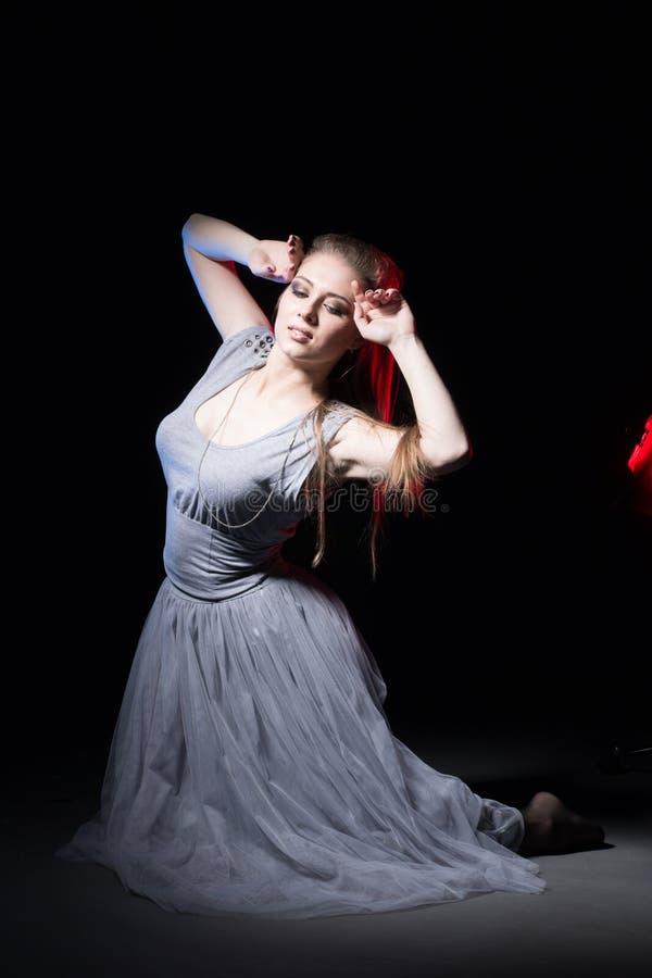 Actrice in een grijze kleding op een donker stadium royalty-vrije stock foto's