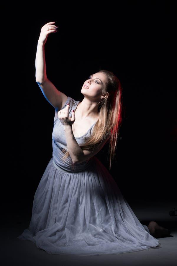 Actrice in een grijze kleding op een donker stadium stock afbeeldingen
