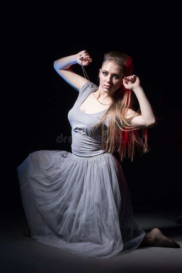 Actrice in een grijze kleding op een donker stadium stock fotografie