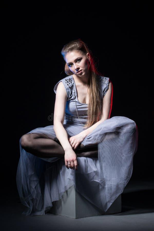 Actrice in een grijze kleding op een donker stadium royalty-vrije stock fotografie