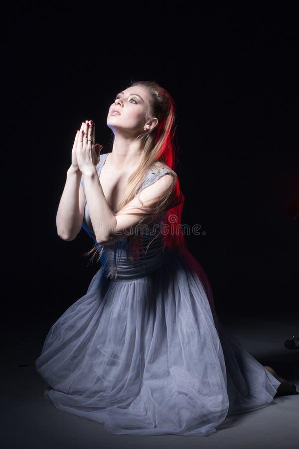 Actriz en un vestido gris en una etapa oscura foto de archivo libre de regalías