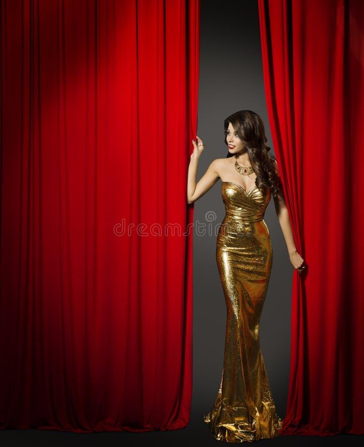 Actriz que abre la cortina roja del cine, vestido del oro de la mujer imagen de archivo