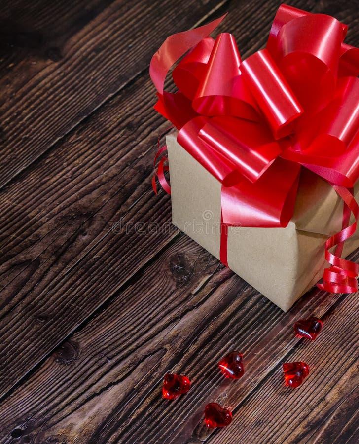 Actual caja con la cinta roja del arco y jugar a hockey shinny pocos corazones en un fondo rústico de madera del tablero para día fotografía de archivo libre de regalías