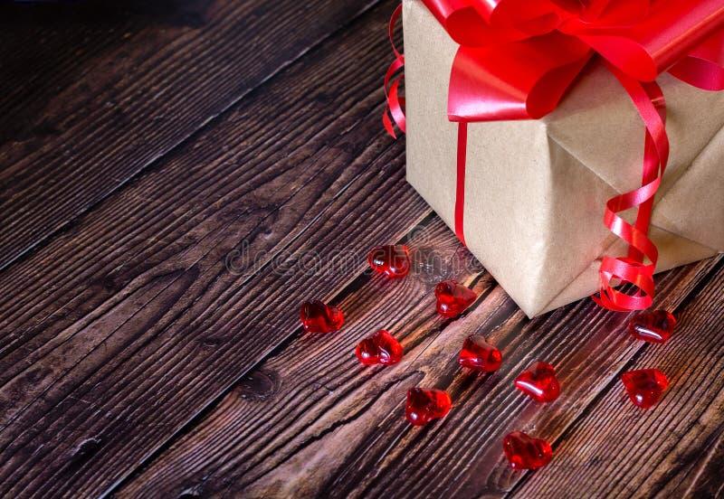 Actual caja con la cinta roja del arco y jugar a hockey shinny pocos corazones en un fondo rústico de madera del tablero para día imagen de archivo libre de regalías