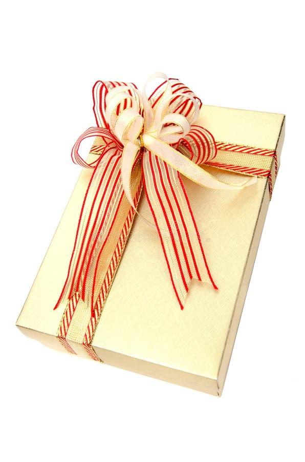 Actual caja de regalo del oro con el arco de forma aplastante aislado en blanco imagen de archivo