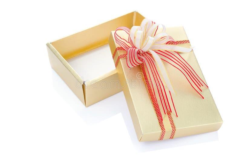 Actual caja de regalo del oro con el arco de forma aplastante aislado en blanco fotos de archivo libres de regalías