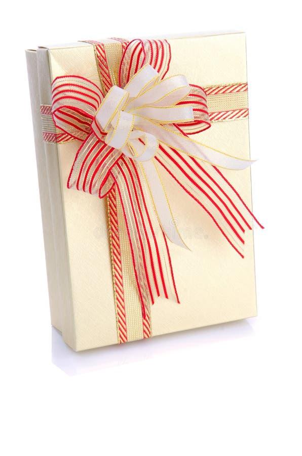 Actual caja de regalo del oro con el arco de forma aplastante aislado en blanco fotos de archivo