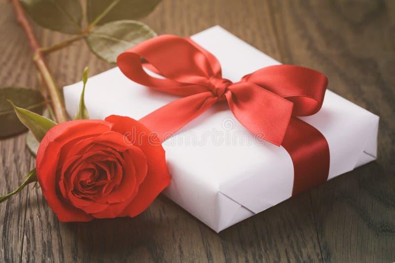 Actual caja rústica con la cinta roja en la tabla de madera imágenes de archivo libres de regalías