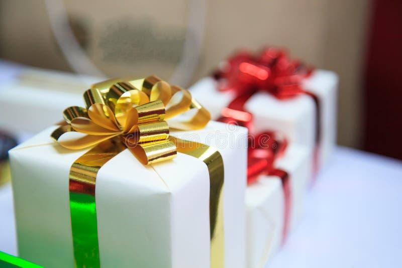 Actual paquete de las cajas con oro y cintas rojas como cajas de regalo de vacaciones por estaciones de donante festivas Gracias, fotos de archivo libres de regalías