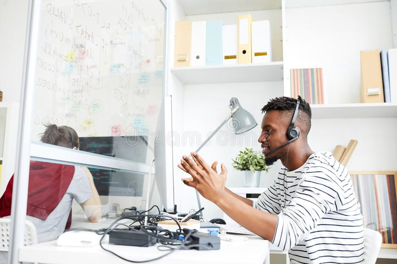 The actual problem is. Young it-specialist in headset explaining someone details of technical problem while sitting in office royalty free stock photography