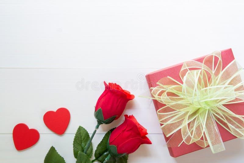 Actual regalo con la caja color de rosa roja de la flor y de regalo con forma de la cinta y del corazón del arco en la tabla de m imagen de archivo