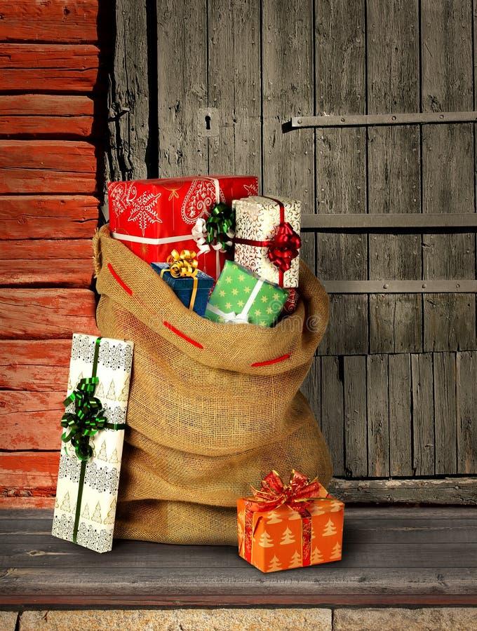 Actual saco de Santas con las cajas de regalo en puerta vieja imagenes de archivo