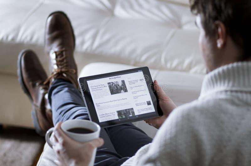 Actualités APP de lecture d'homme sur la Tablette photographie stock libre de droits