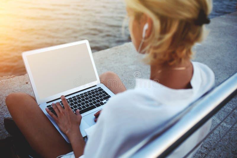 Actualités de lecture de jeune femme par l'intermédiaire d'ordinateur portable tout en se reposant près de la mer pendant ses vac image libre de droits