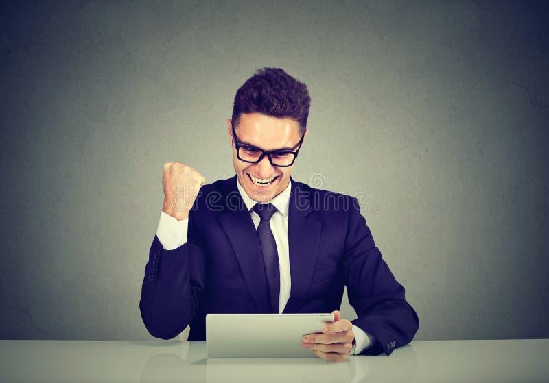 Actualités de lecture enthousiastes d'homme d'affaires bonnes sur la ligne sur une tablette image stock