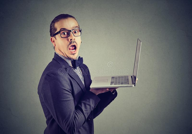 Actualités drôles choquées de lecture d'homme sur l'ordinateur portable photo libre de droits