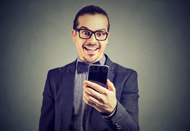 Actualités enthousiastes de lecture d'homme sur le smartphone photographie stock