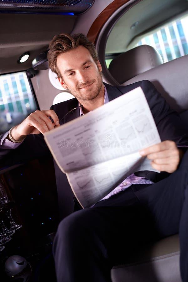 Actualités futées de lecture d'homme dans la limousine photo stock