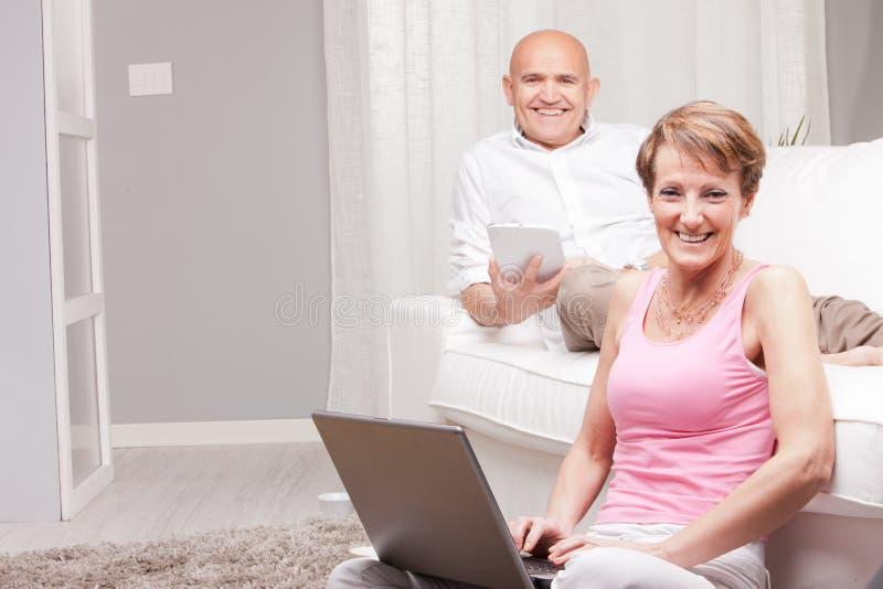 Actualités mûres de lecture de couples dans des dispositifs numériques photographie stock