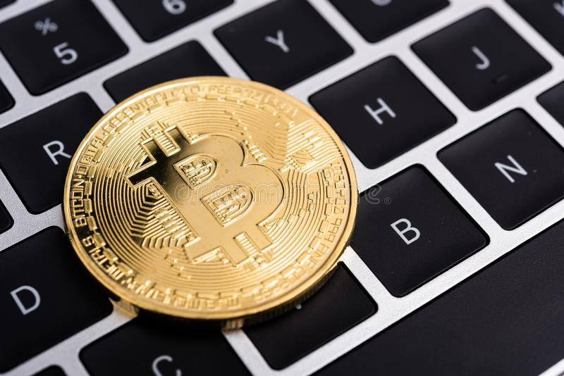 Acuñe, dinero de oro virtual del bitcoin en el ordenador portátil del teclado, imagen de archivo